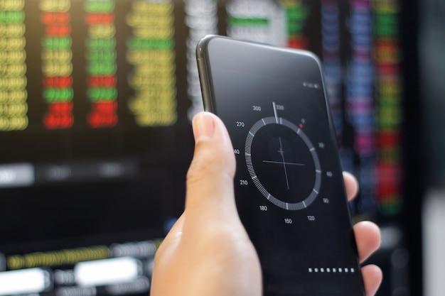Бизнесмен держа smartphone показывая компас, и данные анализируя с использованием диаграммы фондовой биржи компьтер-книжки на экране. финансовые данные и концепция технологии.