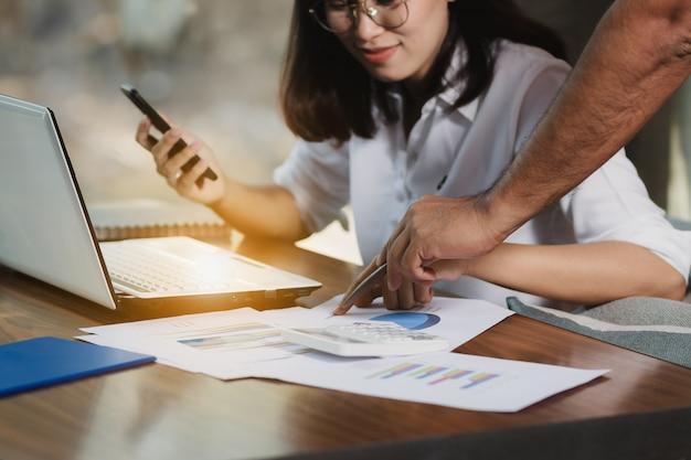 Женщина азии используя smartphone, пк работая с друзьями счастливо.