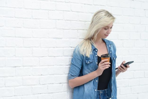 Молодая коммерсантка используя smartphone и держащ кофейную чашку с белой предпосылкой стены