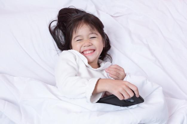 Взгляд сверху маленького ребенка азии имея потеху играя smartphone лежа на кровати утром на смеяться над мягких подушек чувствует счастливым.