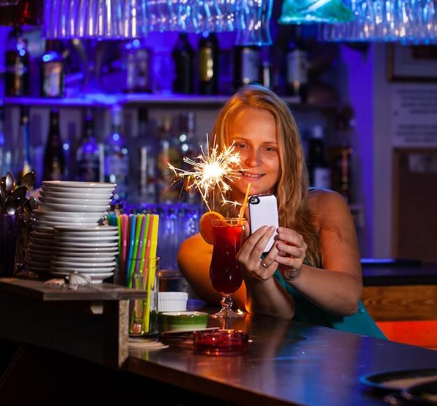 Женщина фотографируя с ее smartphone к коктеилю с бенгальским огнем