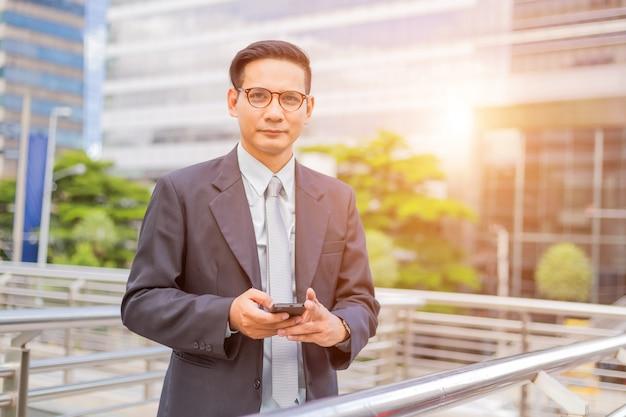 Бизнесмен азии молодой красивый с его smartphone стоя на дорожке современного города.