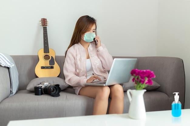 Азиатская молодая женщина фрилансера говоря на smartphone и используя компьтер-книжку нося защитную маску пока сидящ на софе дома. чистка рук с дезинфицирующим гелем, карантин от коронавируса.