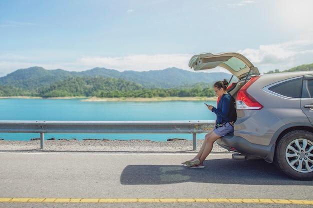 Путешественник женщины один на дороге с сидеть на автомобиле хэтчбека и играть smartphone