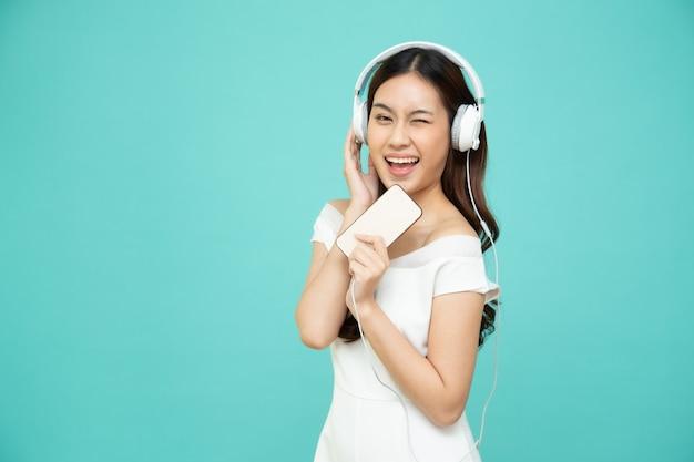 Молодая азиатская женщина красотки слушая с наушниками в приложении песни плейлиста на smartphone изолированном на зеленой стене
