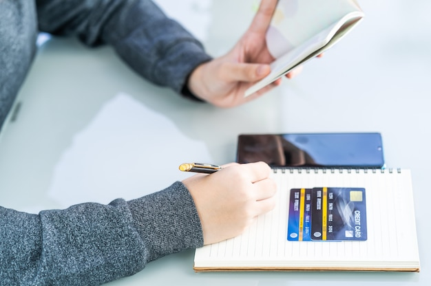 Сочинительство женщины на тетради с столом кредитной карточки и smartphone