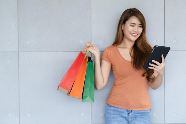 Молодая красивая счастливая азиатская женщина стоя с смайликом использует smartphone или таблетку и носит хозяйственные сумки