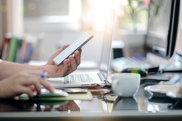 Подрезанная съемка руки человека используя smartphone пока сидящ на столе офиса и работающ с портативным компьютером.