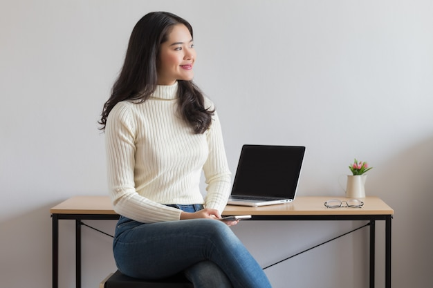 Молодая счастливая азиатская женщина используя smartphone
