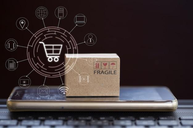 Онлайн покупки, концепция электронной коммерции: картонная коробка с smartphone на клавиатуре тетради и сетевом соединении клиента значка. обслуживание товара и доставка потребителю через интернет.