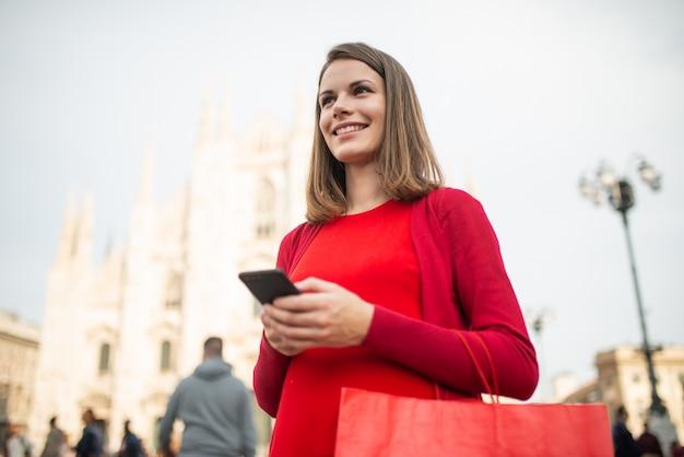 Ходя по магазинам женщина гуляя в город пока использующ ее smartphone