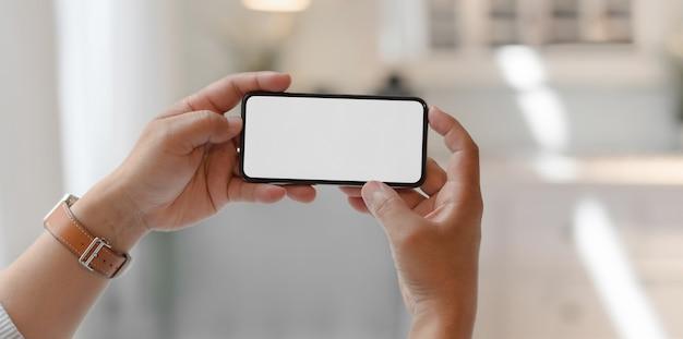 Взгляд конца-вверх человека держа горизонтальный smartphone пустого экрана