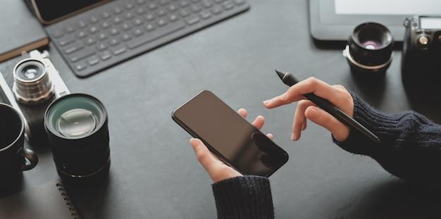 Взгляд конца-вверх женского фотографа держа smartphone в темном стильном рабочем месте