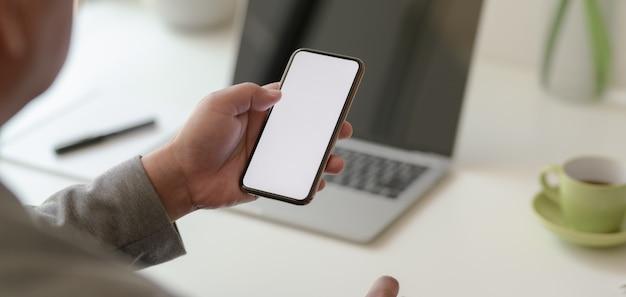 Взгляд конца-вверх профессионального бизнесмена держа smartphone пустого экрана