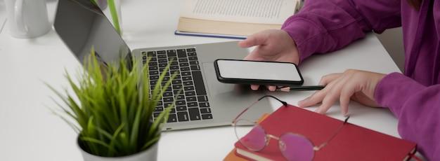 Взгляд со стороны молодой ученицы колледжа ослабляя с smartphone модель-макета на минимальном рабочем пространстве