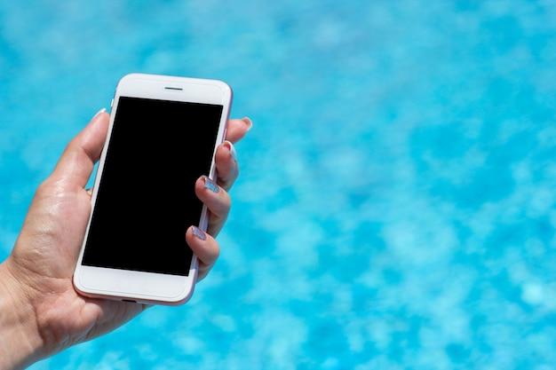 Рука женщины используя smartphone около бассейна, конца-вверх