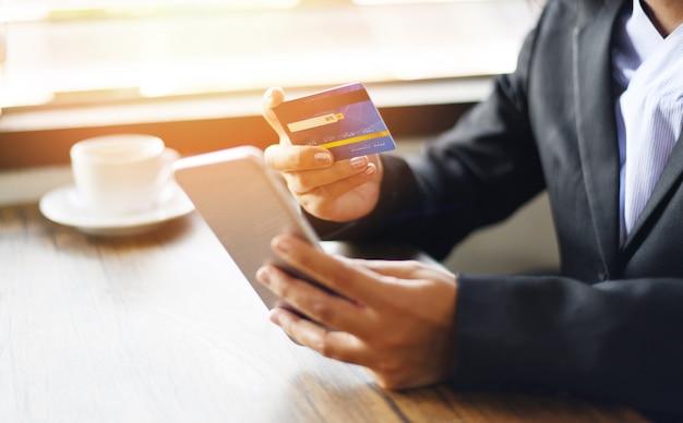 Руки бизнес-леди держа кредитную карточку и используя smartphone для делать покупки люди онлайн оплачивая технологию