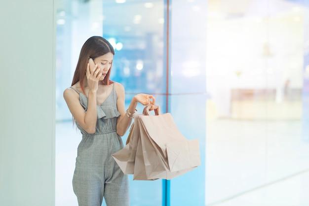 Красивая молодая счастливая азиатская женщина с красочной хозяйственной сумкой используя smartphone пока ходящ по магазинам в моле