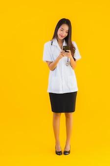 Портрет красивой молодой азиатской женщины доктора использует smartphone