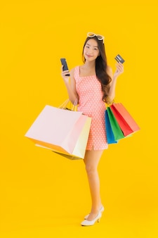 Женщина портрета красивая молодая азиатская с красочной хозяйственной сумкой с smartphone и кредитной карточкой