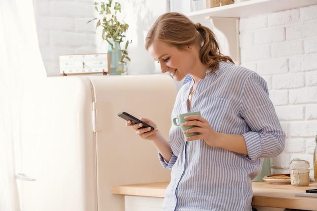 Молодая женщина используя smartphone полагаясь на кухонном столе с кружкой кофе и организатором в современном доме. улыбается женщина, чтение телефонного сообщения. девушка брюнет счастливая печатая текстовое сообщение.