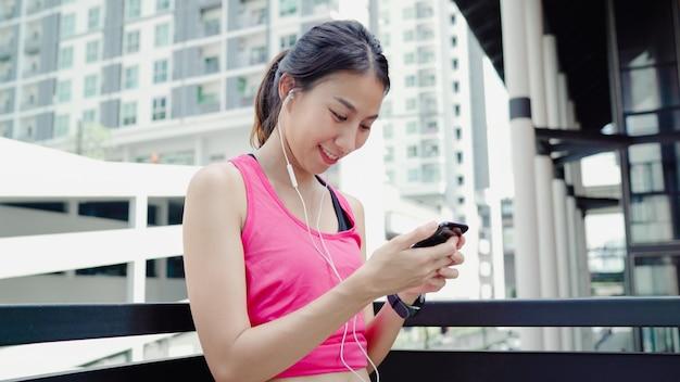 Здоровая красивая молодая азиатская женщина спортсмена используя smartphone для слушает музыка пока бегущ