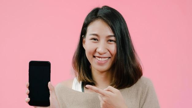 Молодая азиатская женщина используя smartphone проверяя социальные средства массовой информации чувствуя счастливый усмехаться в вскользь одежде над розовой предпосылкой