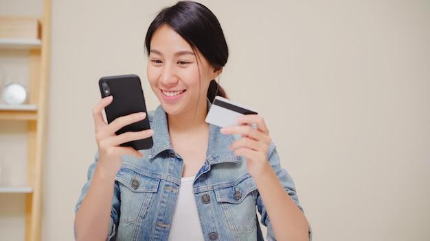 Красивая азиатская женщина используя smartphone покупая онлайн покупки кредитной карточкой пока носка вскользь сидя на столе в живущей комнате дома.