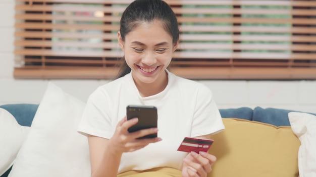 Молодая усмехаясь азиатская женщина используя smartphone покупая онлайн покупки кредитной карточкой