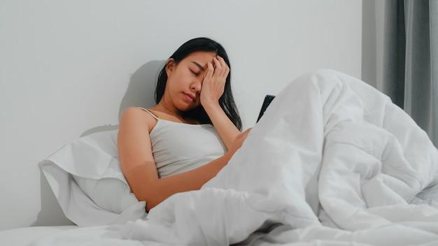 Молодая азиатская женщина используя smartphone проверяя социальные средства массовой информации чувствуя счастливый усмехаться пока лежащ на кровати после бодрствования в утре, красивый привлекательный усмехаться испанской дамы ослабляет в спальне дома.