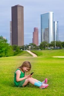 Белокурая девушка ребенк играя при smartphone сидя на лужайке парка на горизонте города