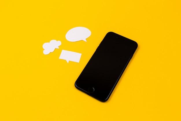 Смартфоны с бумажной речи пузыри на желтом фоне. концепция связи. вид сверху. копировать пространство бумажная композиция