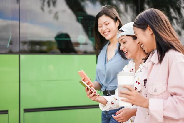 Счастливые азиатские друзья используя smartphones на автобусной станции. молодые студенты люди веселятся с приложением телефонов после школы