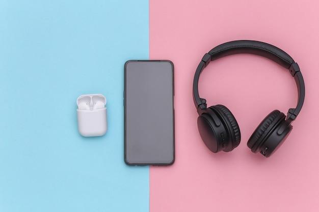 Smartpone、ワイヤレスの大型ステレオヘッドフォン、ピンクブルーのパステルカラーの背景に充電ケース付きの小型イヤフォン。上面図