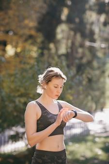 Женщина, используя ее сенсорный экран smartwatch носимых технологий устройства в утренних огнях