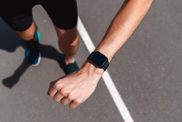 Частичный вид спортивного молодого спортсмена, показывающего smartwatch с пустым экраном на беговой дорожке
