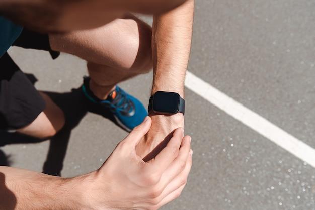 Частичный вид спортивного молодого спортсмена, смотрящего на smartwatch на беговой дорожке в солнечный день