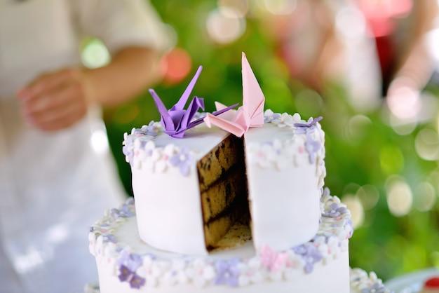 いくつかの紙の鳥との結婚式で、外側にクリーム、内側にチョコレートを入れたスマッシュケーキxa