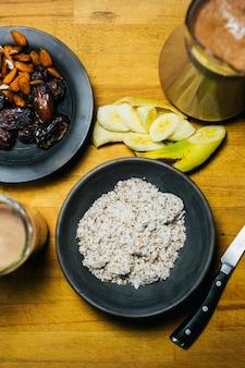 自然で健康的なジュースの準備ができている木製のテーブルにアーモンド、バナナ、ナツメヤシの果実を粉砕