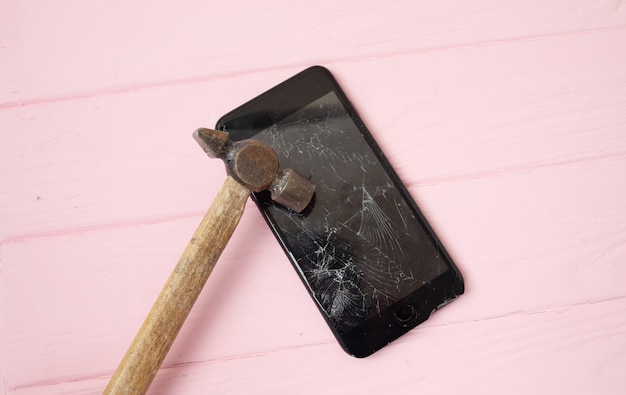 Smashed phone screen on a table with a hammer