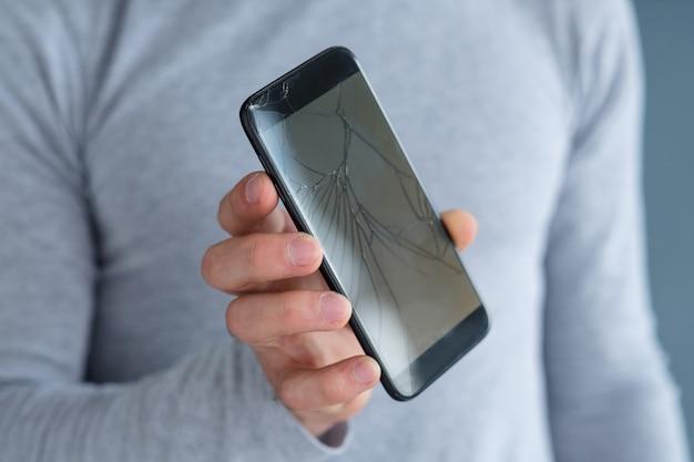 粉々に砕け散ったひびの入った画面。破損したスマートフォンを持っている男