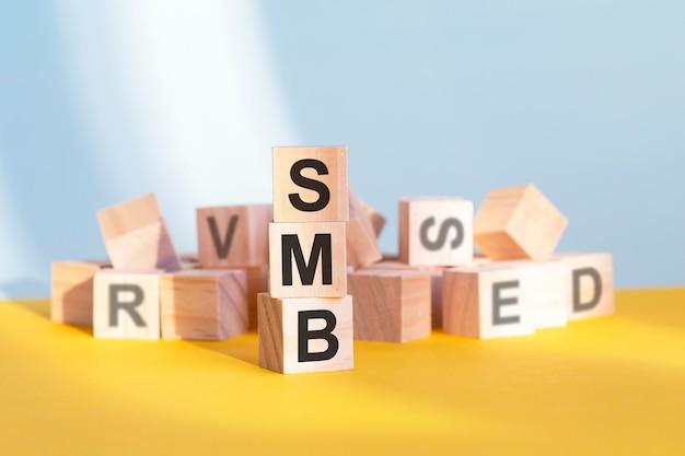 나무 큐브에 작성된 smb - 수직 피라미드, 회색 및 노란색 배경 배열, smb - server message block의 약자, 비즈니스 개념