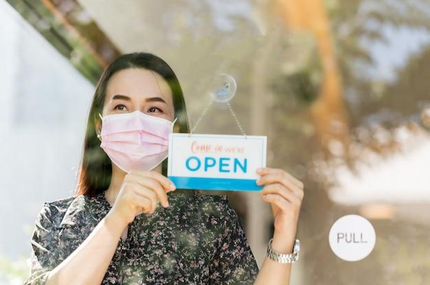중소기업 경영자 여성이 커피 숍과 음식을 오픈하고, 정부가 방역 조치를 완화 한 후 전염병을 예방합니다.