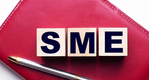 Sme subject matter expert made up of wooden cubes that stand on a burgundy notebook near the pen. business concept