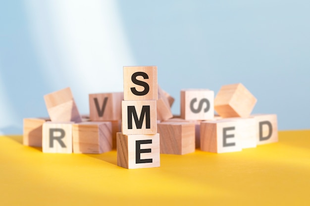 나무 큐브에 쓰여진 sme - 수직 피라미드, 회색 및 노란색 배경으로 배열, sme - 중소기업용 약어, 비즈니스 개념