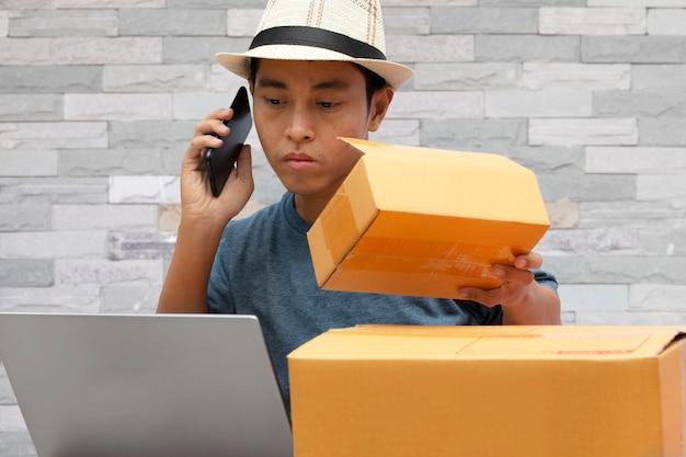 中小企業smeのオンライン販売のアイデア、スマートフォンを使用しているアジア人男性がオンライン購入のショッピング注文を確認しています。