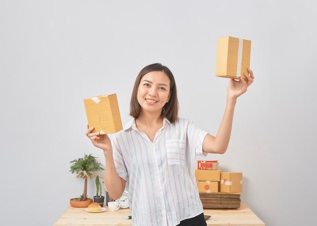パッケージ、ビジネスsme、スタートアップをオンラインで保持している女性
