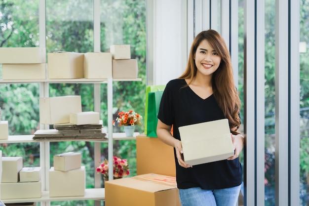 Молодая счастливая азиатская женщина-владелец интернет-магазина sme несет упаковку коробки посылки