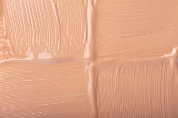 リキッドファンデーションのスミア、ベージュ色。化粧品の背景。