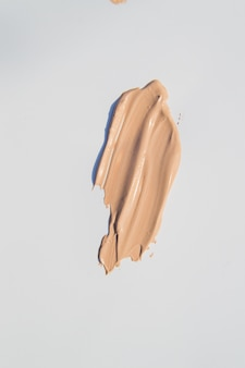 Smeared beige foundation on white background, cosmetic care